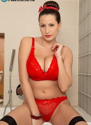 В ванной красивая мамка в чулках снимает красное белье и демонстрирует натуральные сиськи