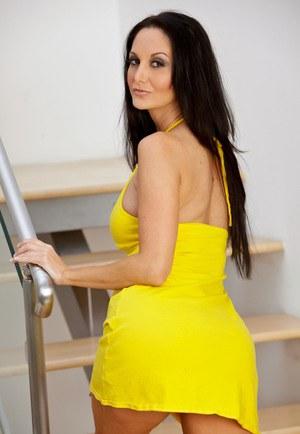Темноволосая мамка с большими сиськами откровенно позирует в сексуальном желтом платье