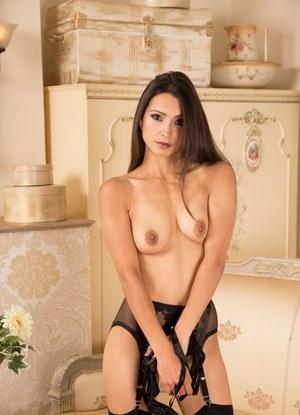 Сексуальная мамка в нижнем белье и чулках на диване раздвигает стройные ножки