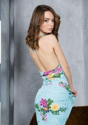 18летняя милашка в студии снимает платье и позирует полностью обнаженной