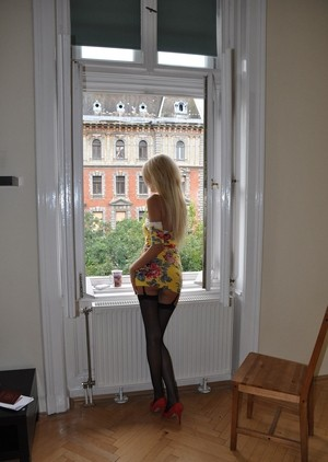 Молодая длинноногая блондинка после стриптиза надела черные чулочки с подвязками