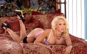 Сексапильная блондинка с большими сиськами расставляет ножки в чулках и гладит пилотку