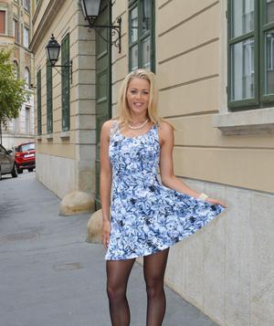 Блондинка снимает короткое платье и остается позировать только в чулочках