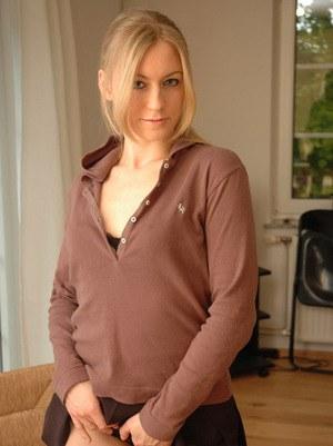 Блондинка в короткой юбочке снимает лифчик и сексуально показывает сиськи