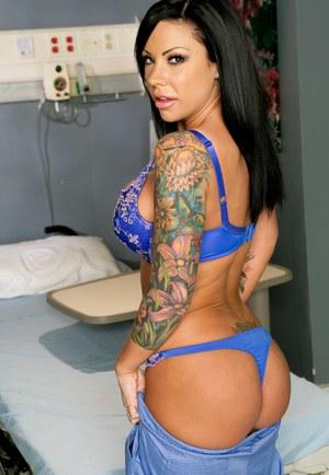 Сисястая татуированная медсестра показывает пациенту в больнице большие буфера