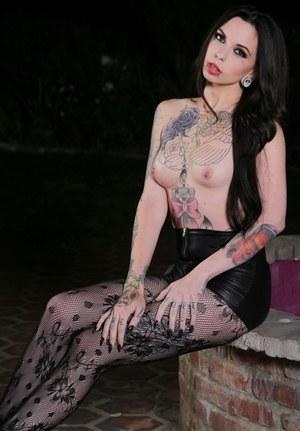 Татуированная брюнетка снимает черные колготки и демонстрирует шикарное тело