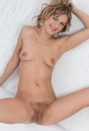 Развратная блондинка пальцами раздвигает половые губы и показывает волосатую пилотку
