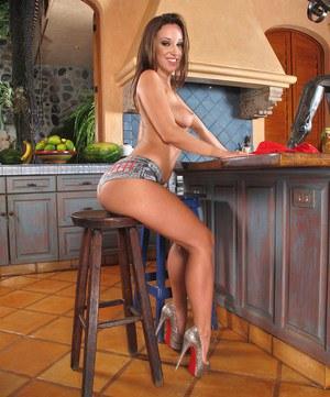 Красотка намазалась маслом и на кухонном столе демонстрирует большую задницу