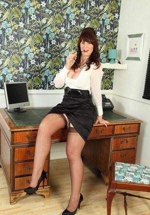 Зрелая секретарша в чулках залезла на стол и светит большой жопой