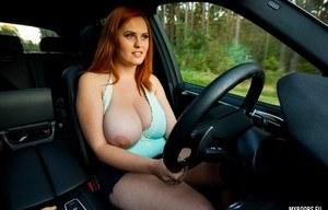 Рыжая развратница за рулем автомобиля снимает платье и ласкает большие сиськи