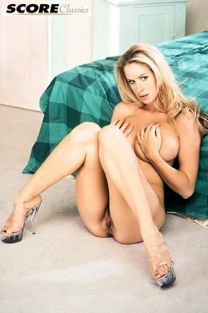 Блондинка с волосами на пилотке снимается для журнала и светит большими сиськами