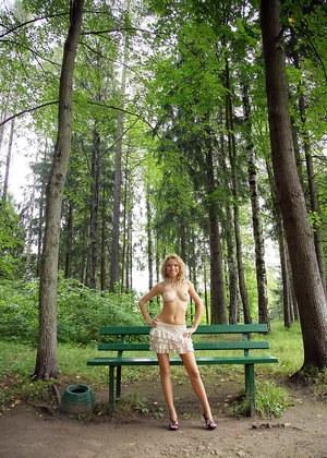 В парке сексуальная блондинка разделась и позирует только в короткой юбочке