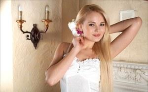 Длинноногая блондинка сняла платье и эротично позирует возле камина