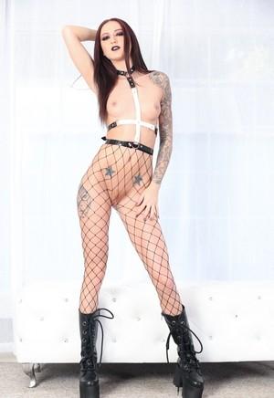 Татуированная девушка гот в сетчатых колготках показывает шикарное тело
