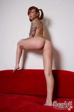 Рыжая татуированная неформалка с гордостью показывает тело с пирсингом на камеру