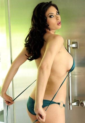 Длинноногая сисястая азиатка снимает узкие трусики и ласкает бритую киску