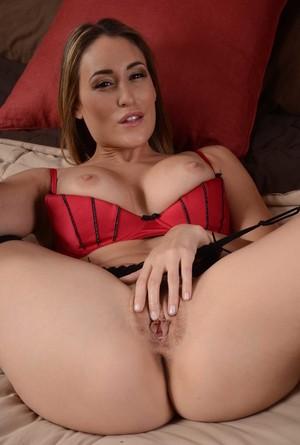 Сексуальная мамка в чулках прилегла на кровать и ласкает бритую киску