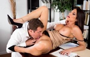 На столе мамка секретарша с большими сиськами жарко трахается с похотливым боссом