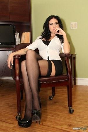 Темноволосая мамка секретарша перед боссом позирует в черных чулках