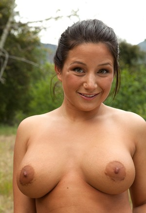На природе сексуальная брюнетка позирует и показывает большие сиськи